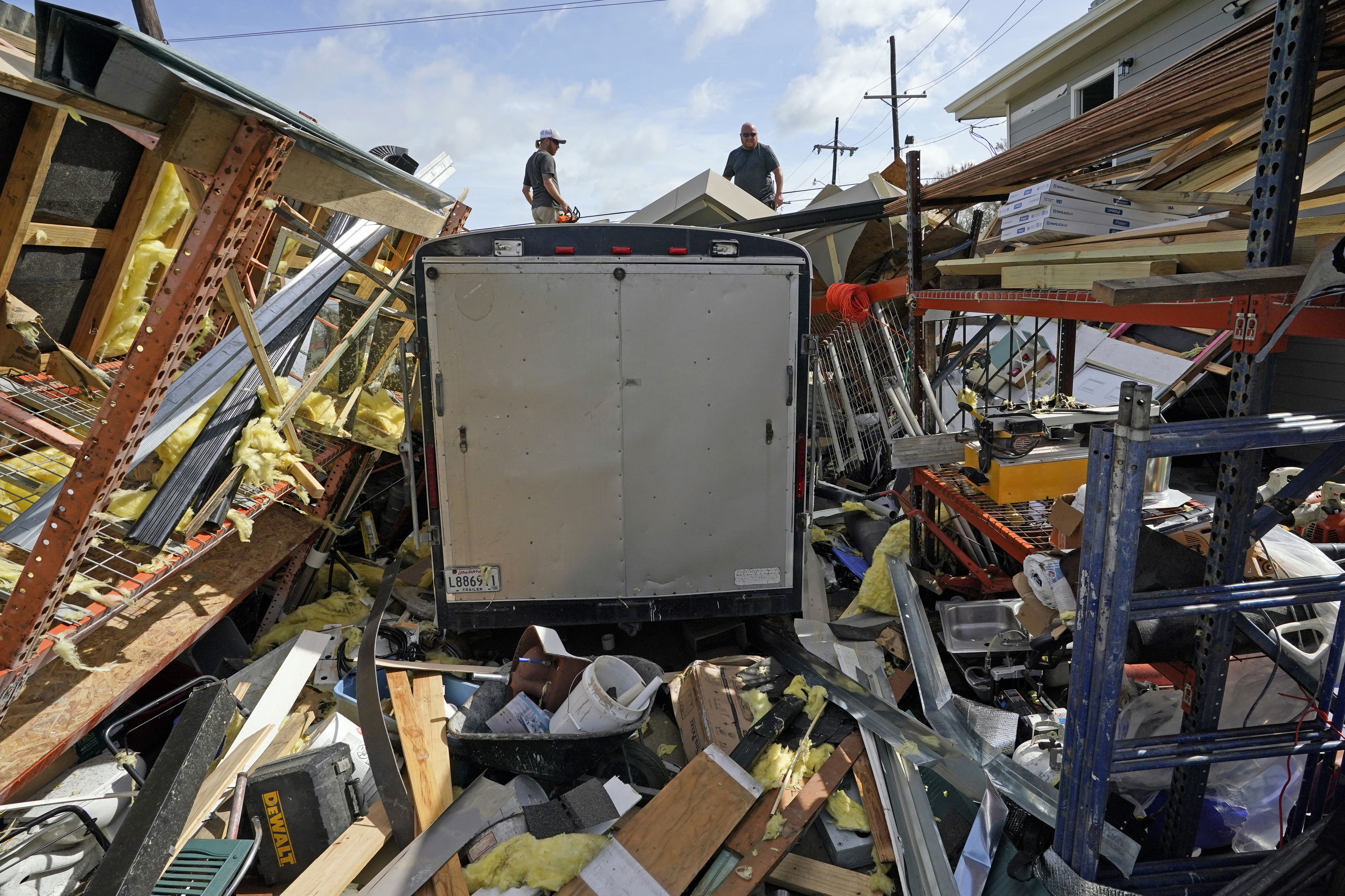Jacob Hodges, right, and his brother Jeremy Hodges work to clear debris from their storage unit which was destroyed by Hurricane Ida.
