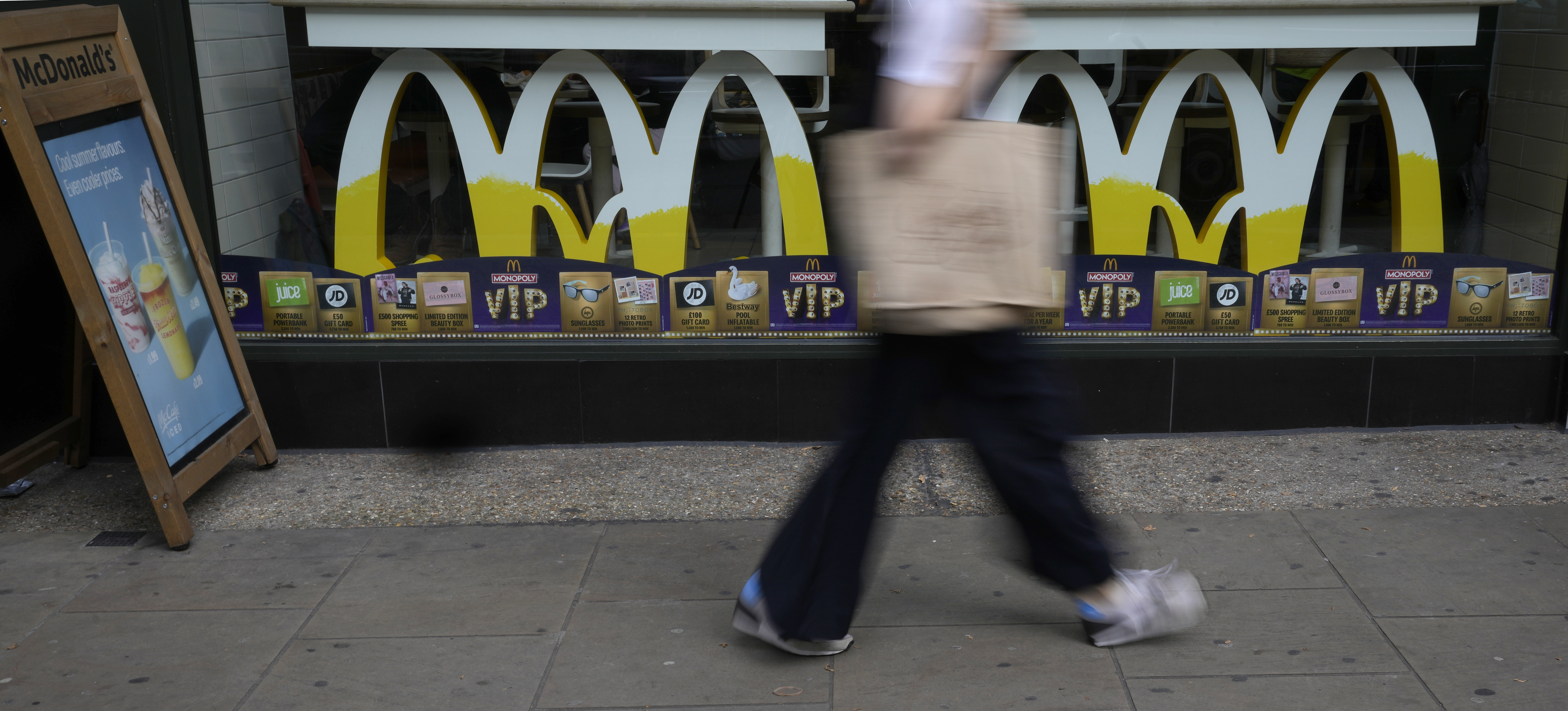 A woman walks by a McDonald's restaurant, in London, Tuesday, Aug. 24, 2021. McDonalds says it has pulled milkshakes from the menu in all 1,250 of its British restaurants because of supply problems stemming from a shortage of truck drivers. The fast-food chain says it is also experiencing shortages of bottled drinks. (AP Photo/Alastair Grant)