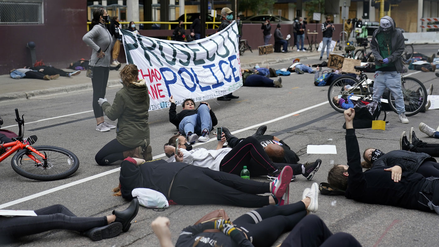 Protesters hold a die-in outside the Hennepin County Family Justice Center where four former Minneapolis police officers appeared at a hearing Friday, Sept. 11, 2020, in Minneapolis
