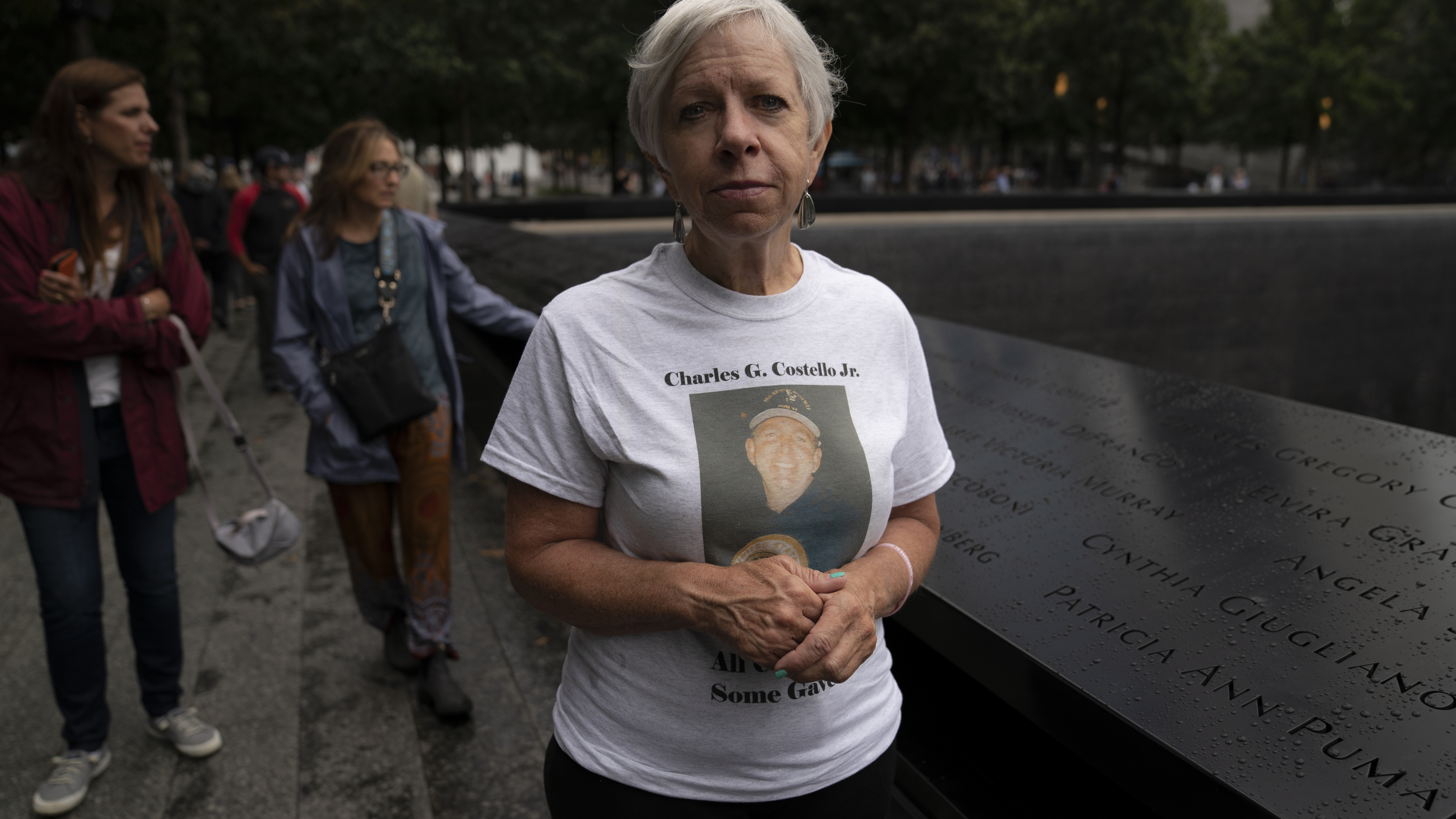 """Kathy Birch, sister of Charles Gregory """"Chuck"""" Costello Jr., an elevator electrician who ran into Tower 1 of the World Trade Center before the towers fell, stands beside her brothers name while visitors browse the north pool at the National September 11 Memorial & Museum in New York."""