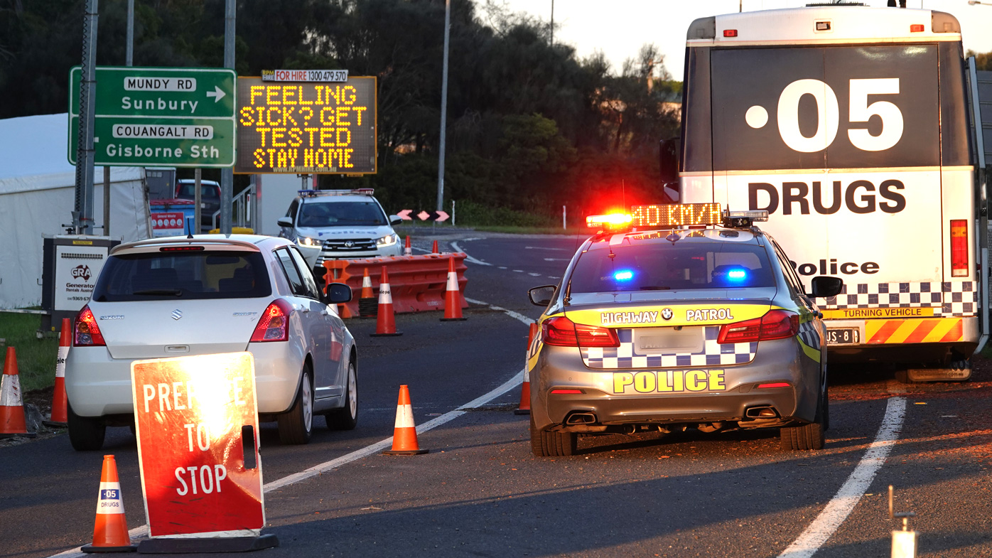 Motorists drive through the 'ring of steel' checkpoint set up by Victoria Police at the border of Sunbury and Gisborne South on the Calder Freeway this morning