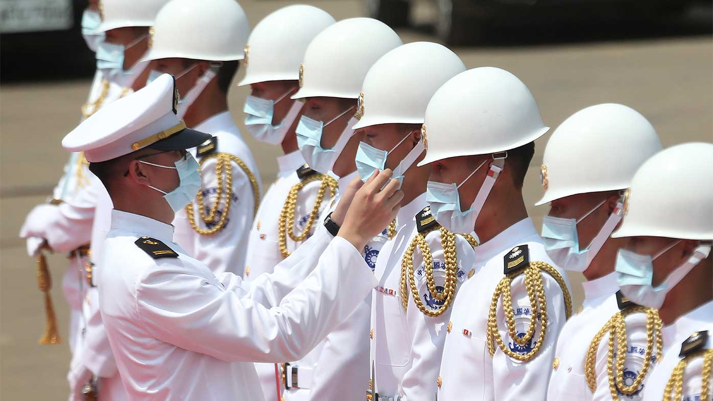 A Taiwan Navy honor guard captain adjusts team member's face mask during a launch ceremony for its first indigenous amphibious transport dock in Kaohsiung, southern Taiwan.