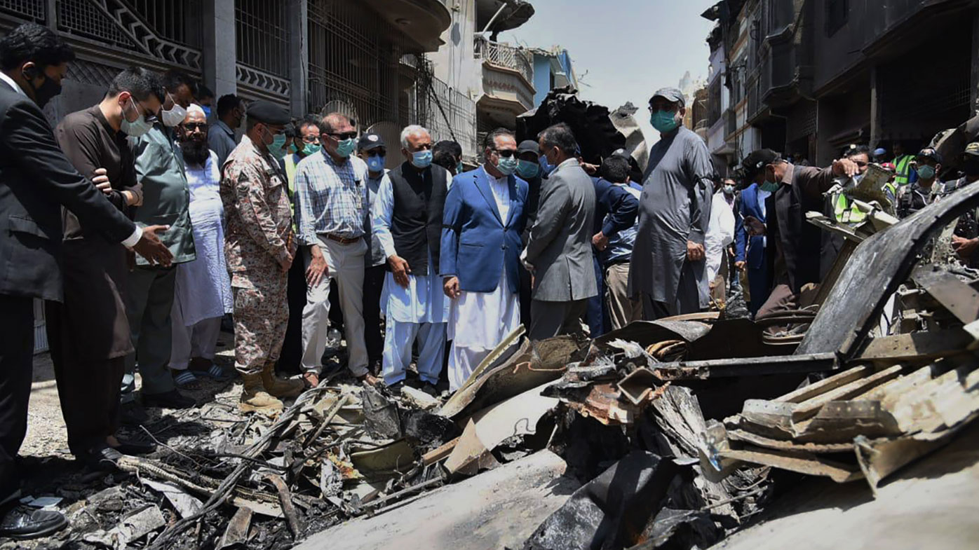 In this photo released by Pakistan Civil Aviation Authority, provincial governor Imran Ismail, center, in blue coat, and Pakistan's aviation minister Ghulam Sarwar, center in black waistcoat, visit the site of Friday's plane crash, in Karachi, Pakistan, Saturday, May 23, 2020