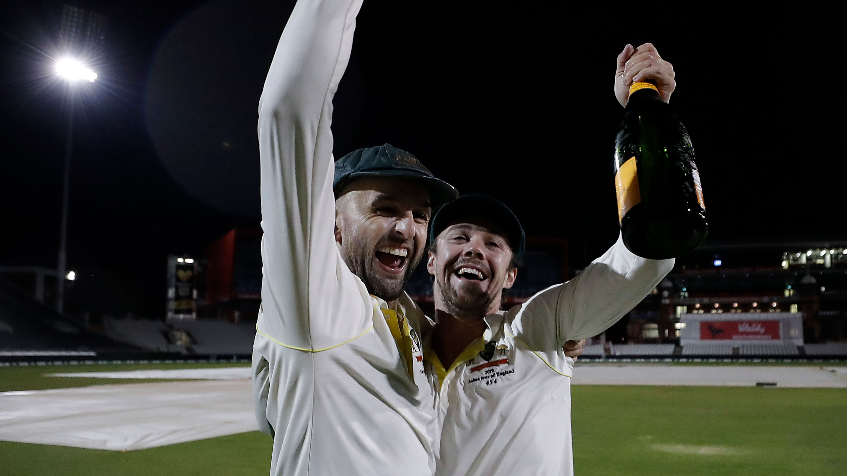 Nathan Lyon and Travis Head share a toast with a bottle of champagne out in the middle.