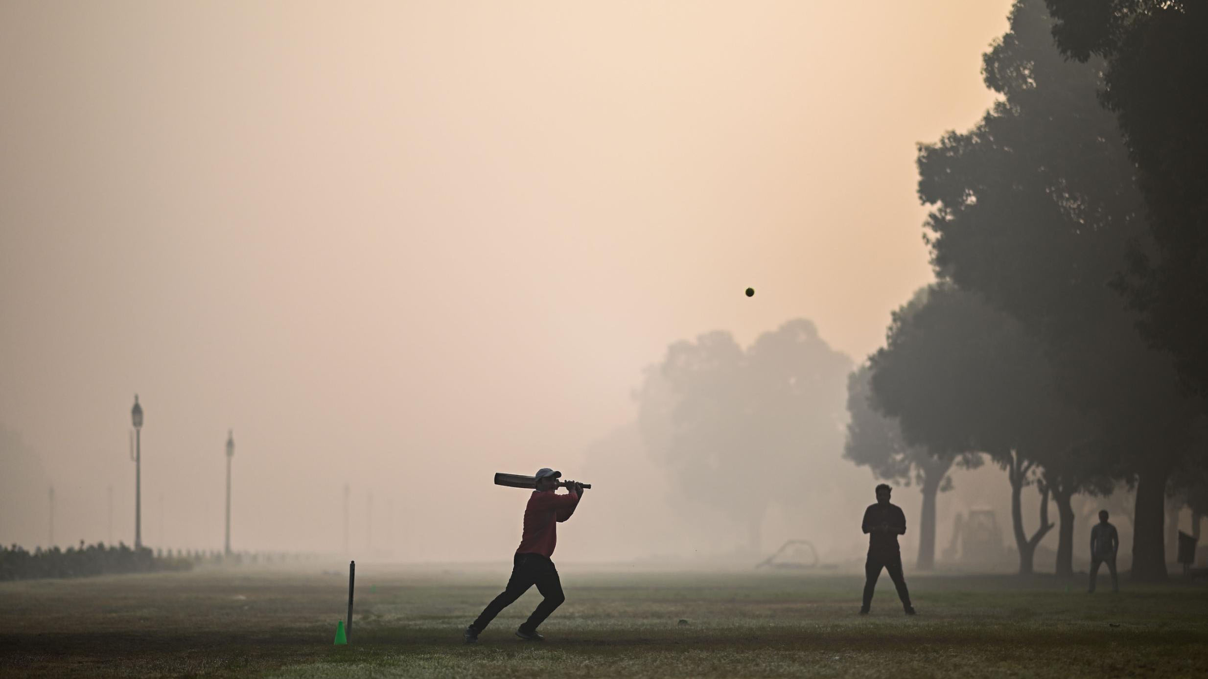 People played cricket at a park in smoky conditions in New Delhi, India.