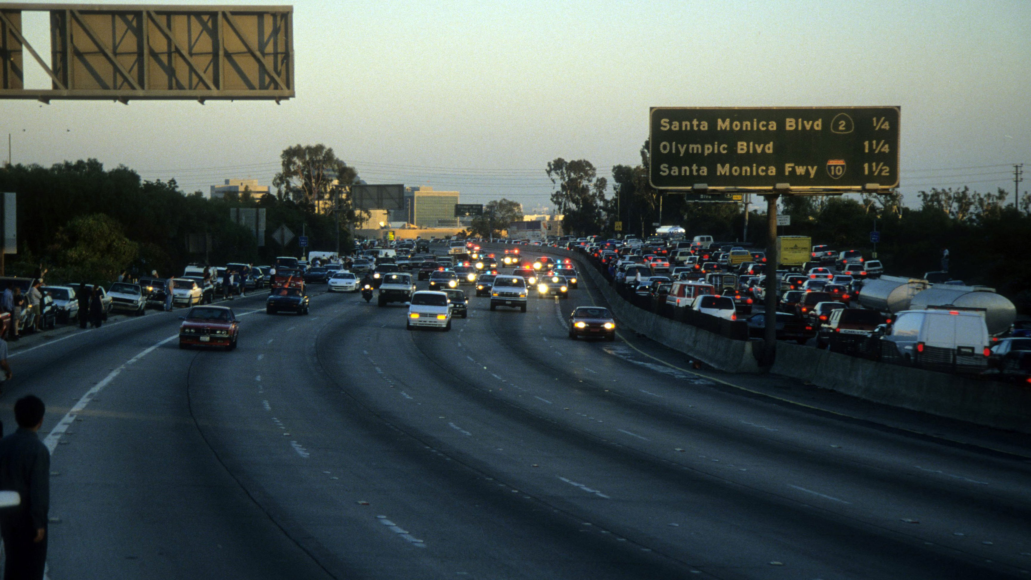 Police cars pursue the Ford Bronco driven by Al Cowlings, carrying then fugitive murder suspect O.J. Simpson, on a slow-speed car chase June 17, 1994 on the 405 freeway in Los Angeles, California. Simpson's friend Cowlings eventually drove Simpson home, with Simpson ducked under the back passenger seat, to Brentwood where he surrendered after a stand-off with police.