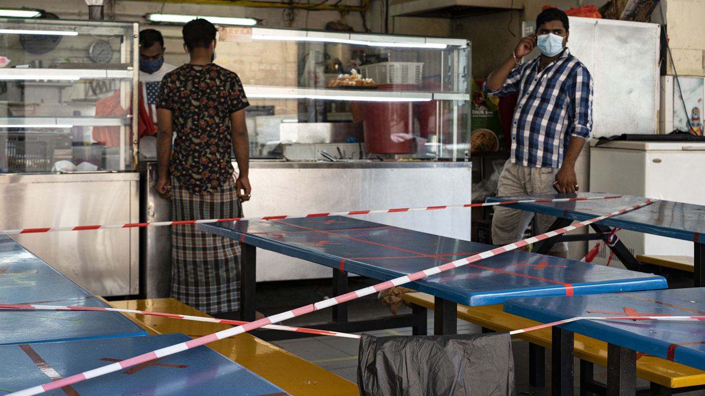 Migrant workers wearing protective face masks walk past tables and chairs in a canteen with barricade.
