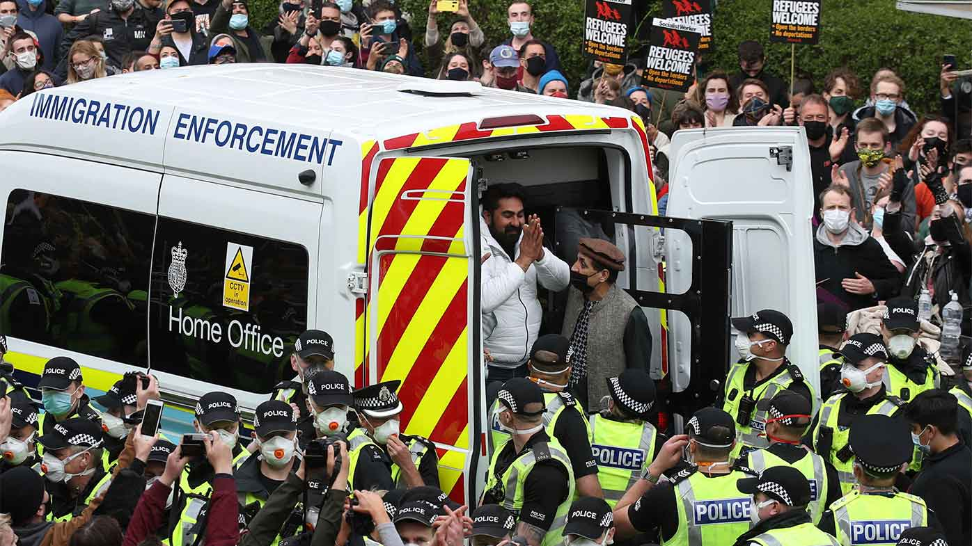 Two men are released from an Immigration Enforcement police van in Glasgow.