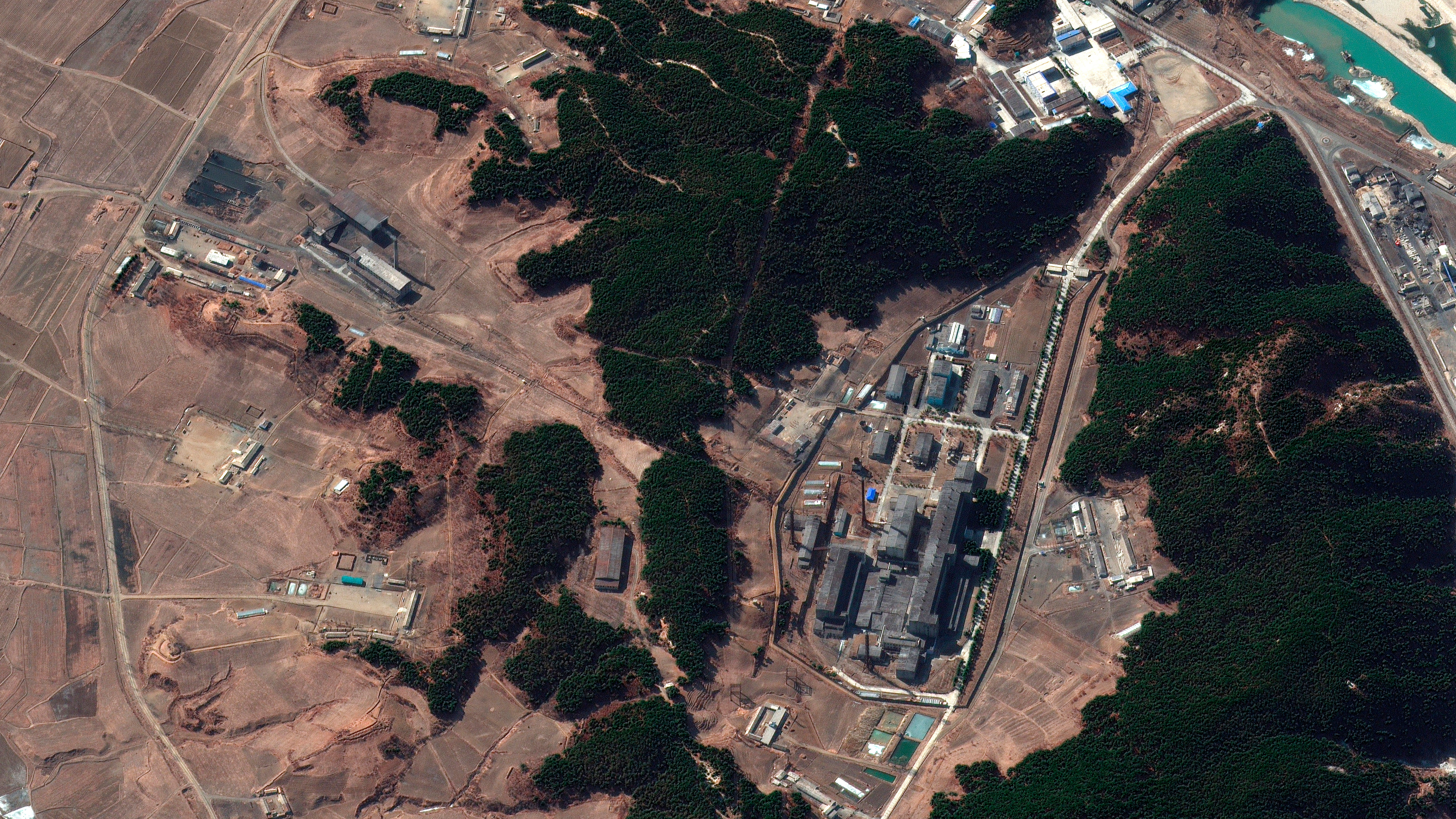 A satellite image taken in March 2021 and provided by Maxar Technologies shows a steam plant, left, and North Korea's main atomic complex, right, in Yongbyon, North Korea. Smoke was observed emanating from the plant's smokestack.
