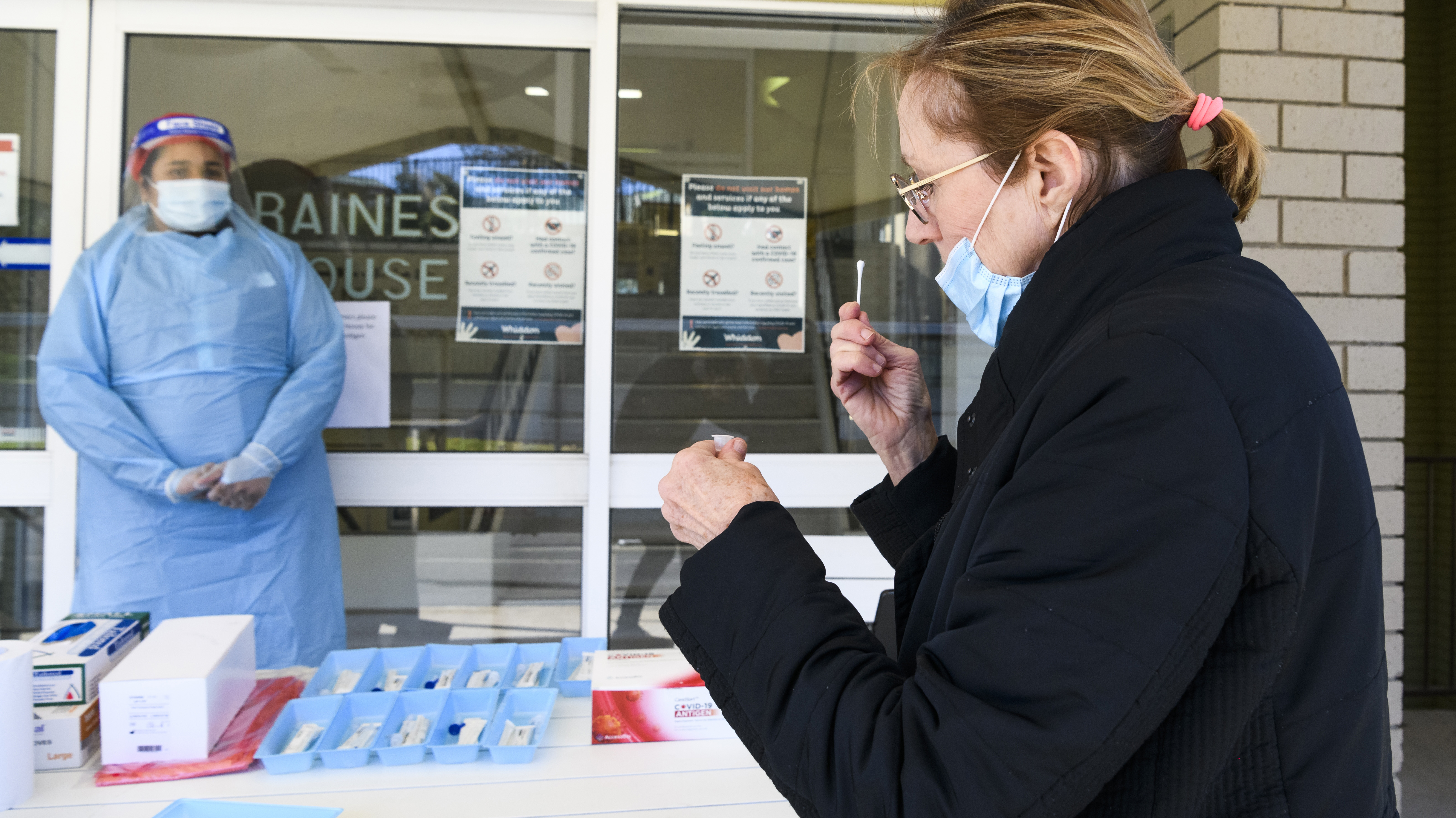 A worker at Whiddon Easton Park Age Care facility in Sydney uses a rapid test.