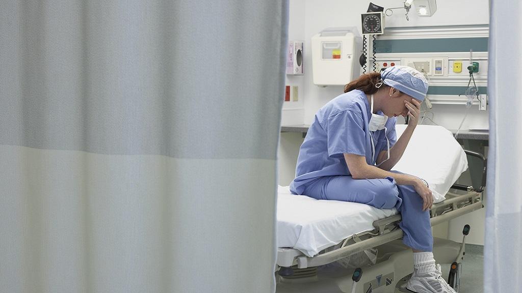 Sad nurse sitting on a hospital bed