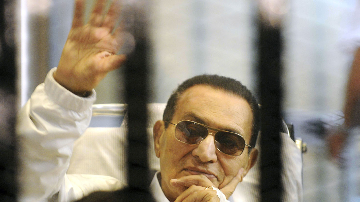 former Egyptian President Hosni Mubarak waves to his supporters from behind bars as he attends a hearing in his retrial on appeal in Cairo, Egypt. (Photo April 2013)