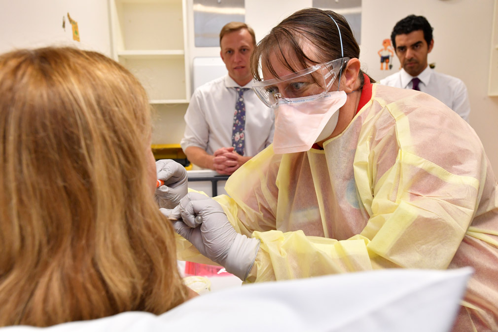 A GP performs a mock coronavirus examination on a patient inside the fever clinic at the Prince Charles Hospital in Brisbane.
