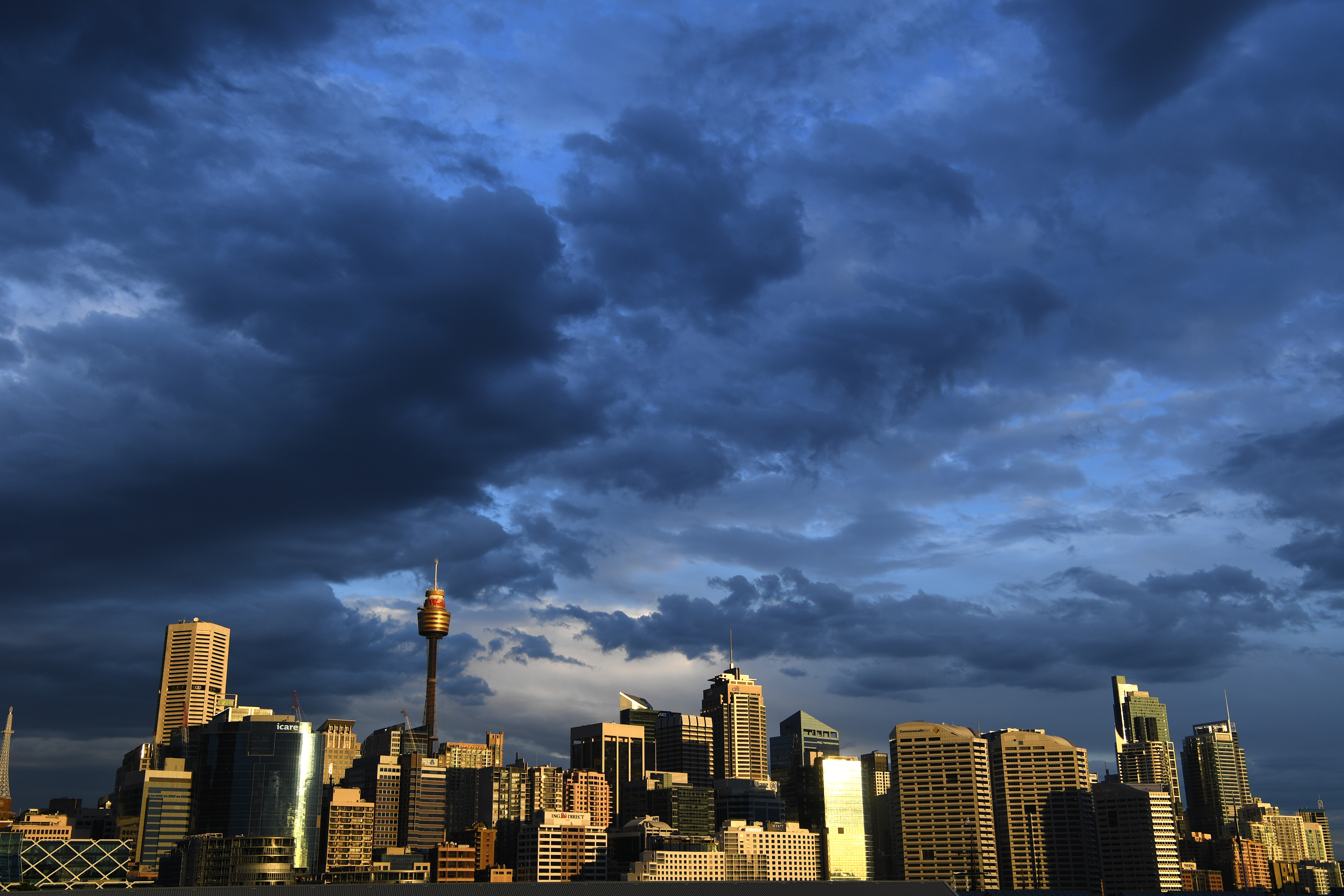 Clouds gather over the Sydney CBD skyline. Workers are expected to return to the office in greater numbers over the coming weeks.