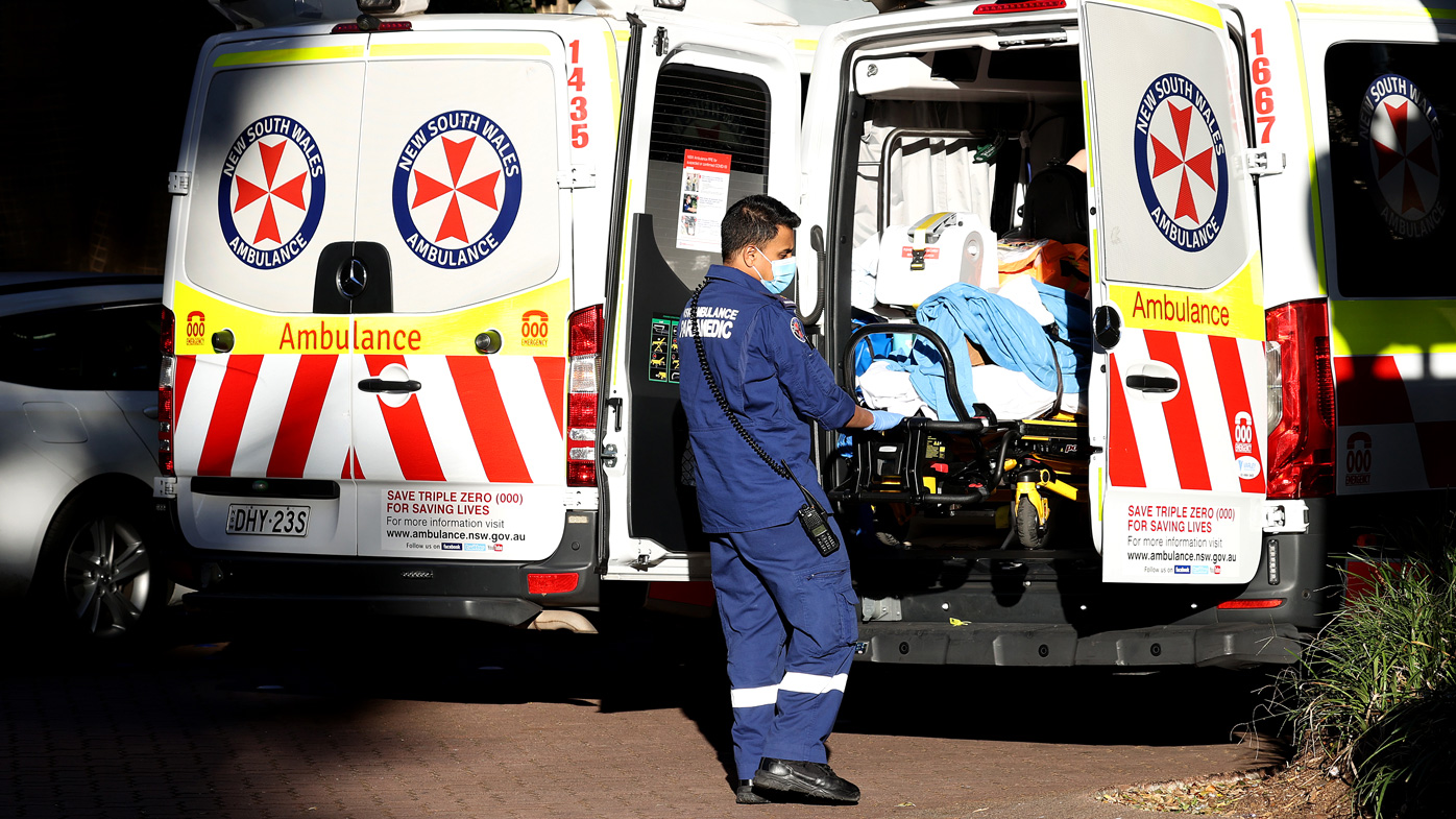 A NSW ambulance paramedic helps a patient into a Sydney hospital.