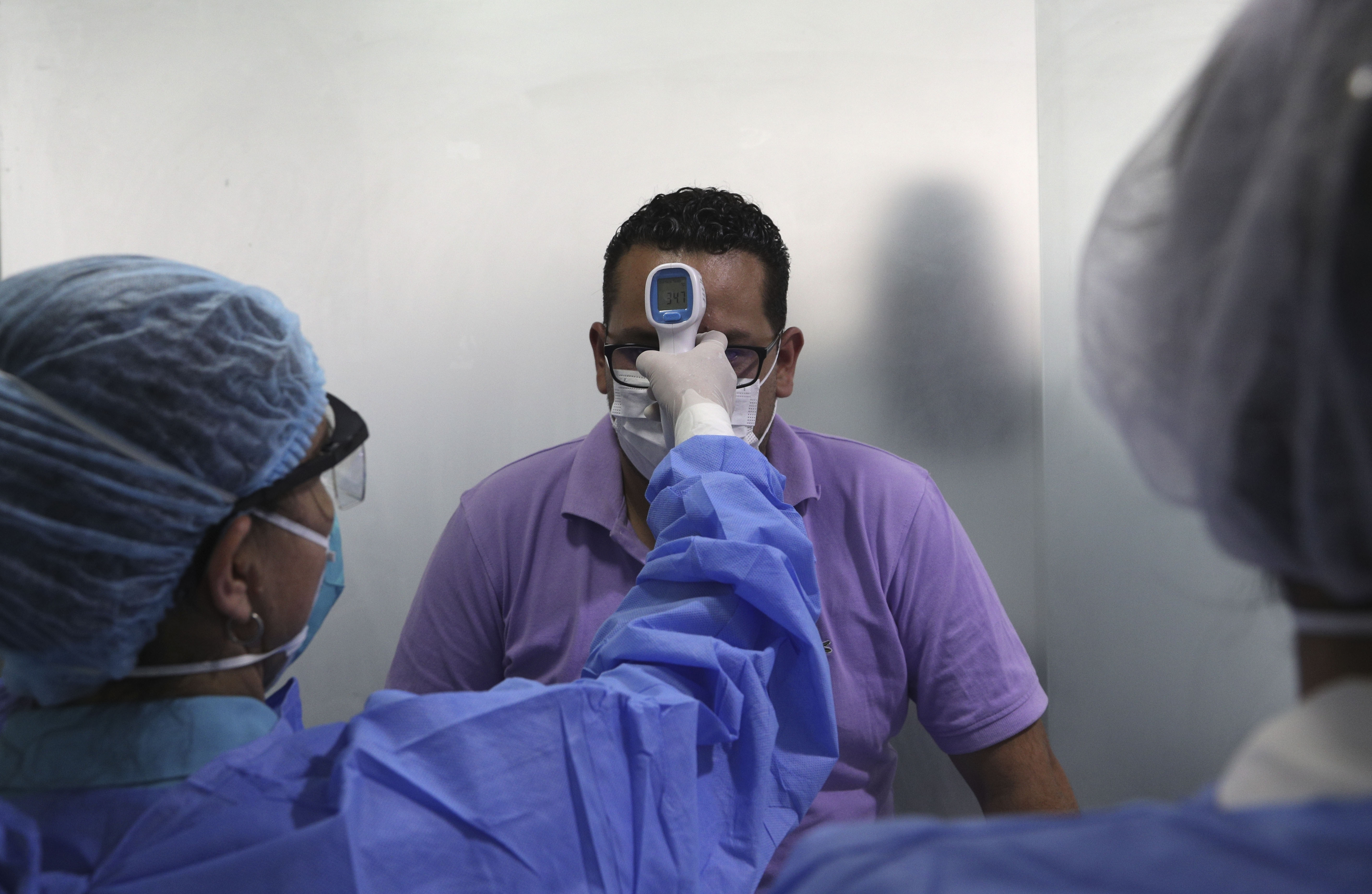 A man wearing a mask as a precautionary measure against the spread of the new coronavirus gets his temperature taken.