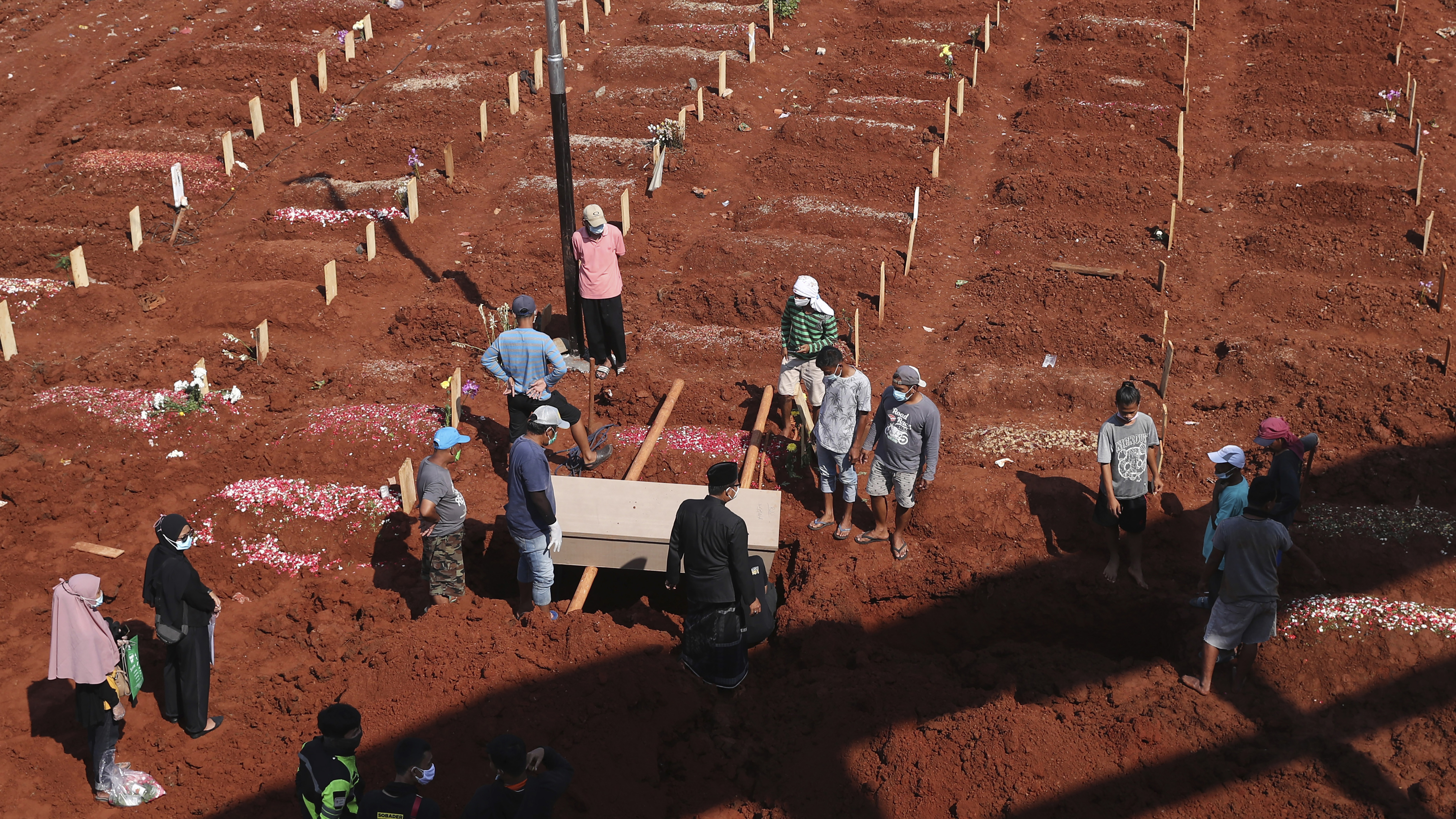 Workers prepare a coffin for burial at the special section of Jombang Public Cemetery reserved for those who died of COVID-19, in Tangerang, on the outskirts of Jakarta, Indonesia.