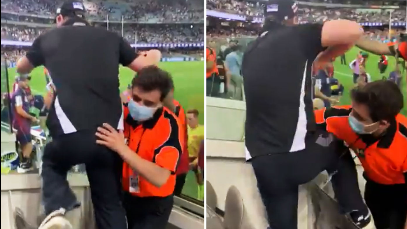 An unruly fan was restrained as he tried to get at umpires. (Twitter)