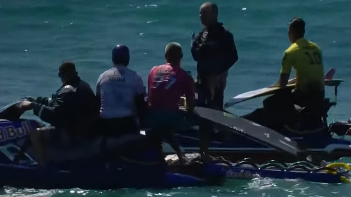 Felipe Toledo and Gabriel Medina are taken from the water after a shark sighting at the WSL finals in California.