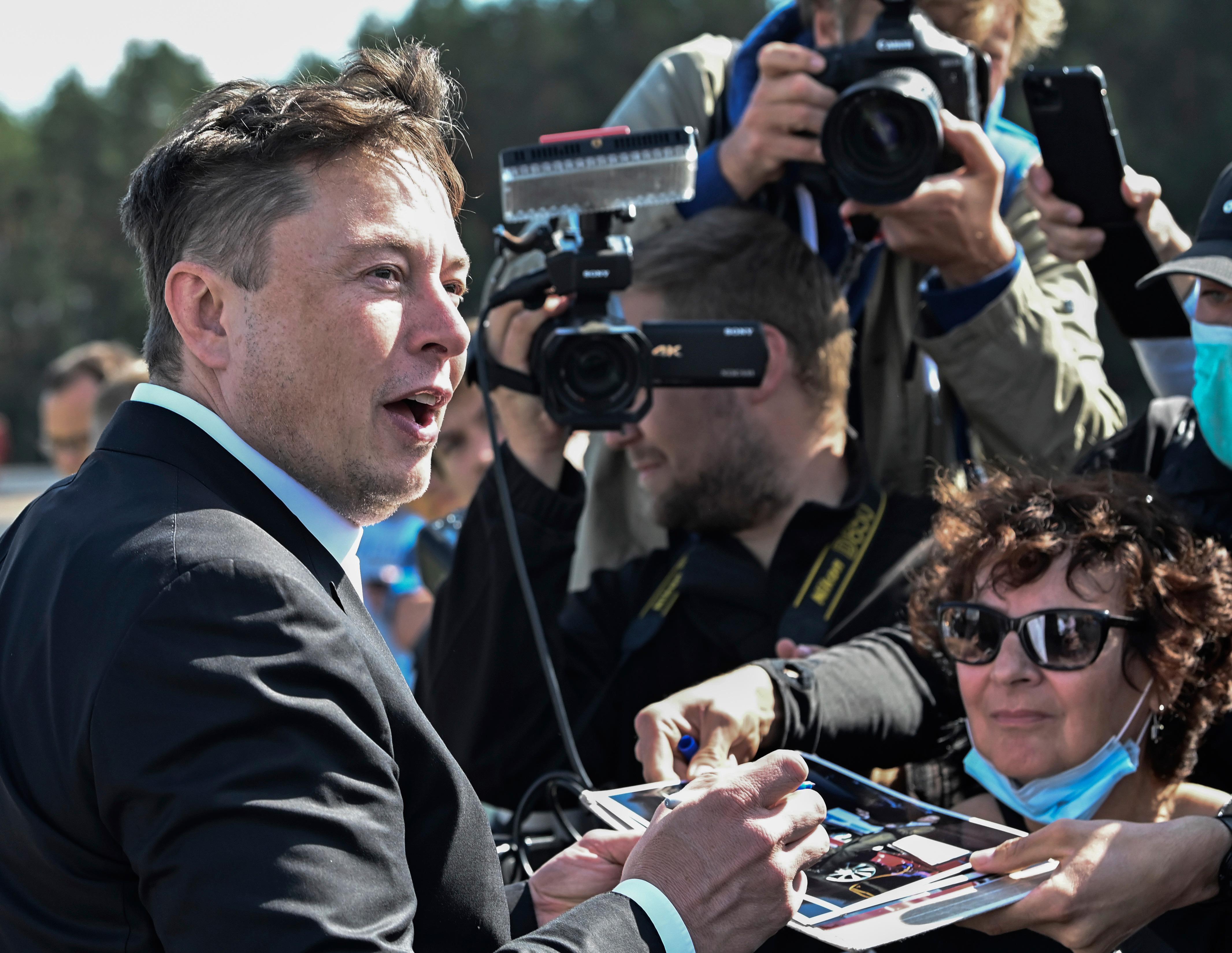 Technology entrepreneur Elon Musk gives autographs as he visits the Tesla Gigafactory construction site in Gruenheide near Berlin