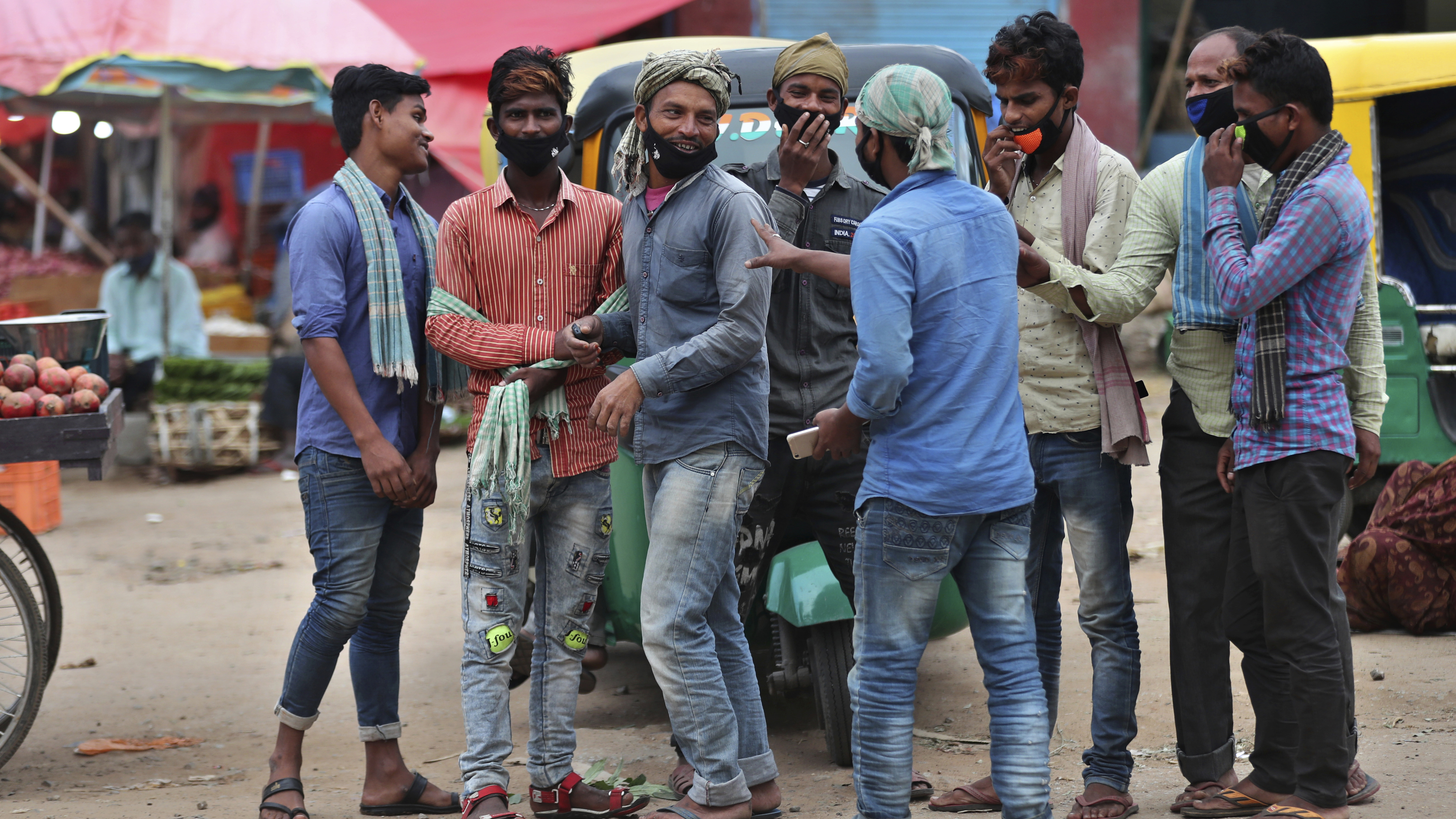 Daily wage laborers wearing face masks as a precaution against the coronavirus stand together as they wait for work at a wholesale market in Bengaluru, India,