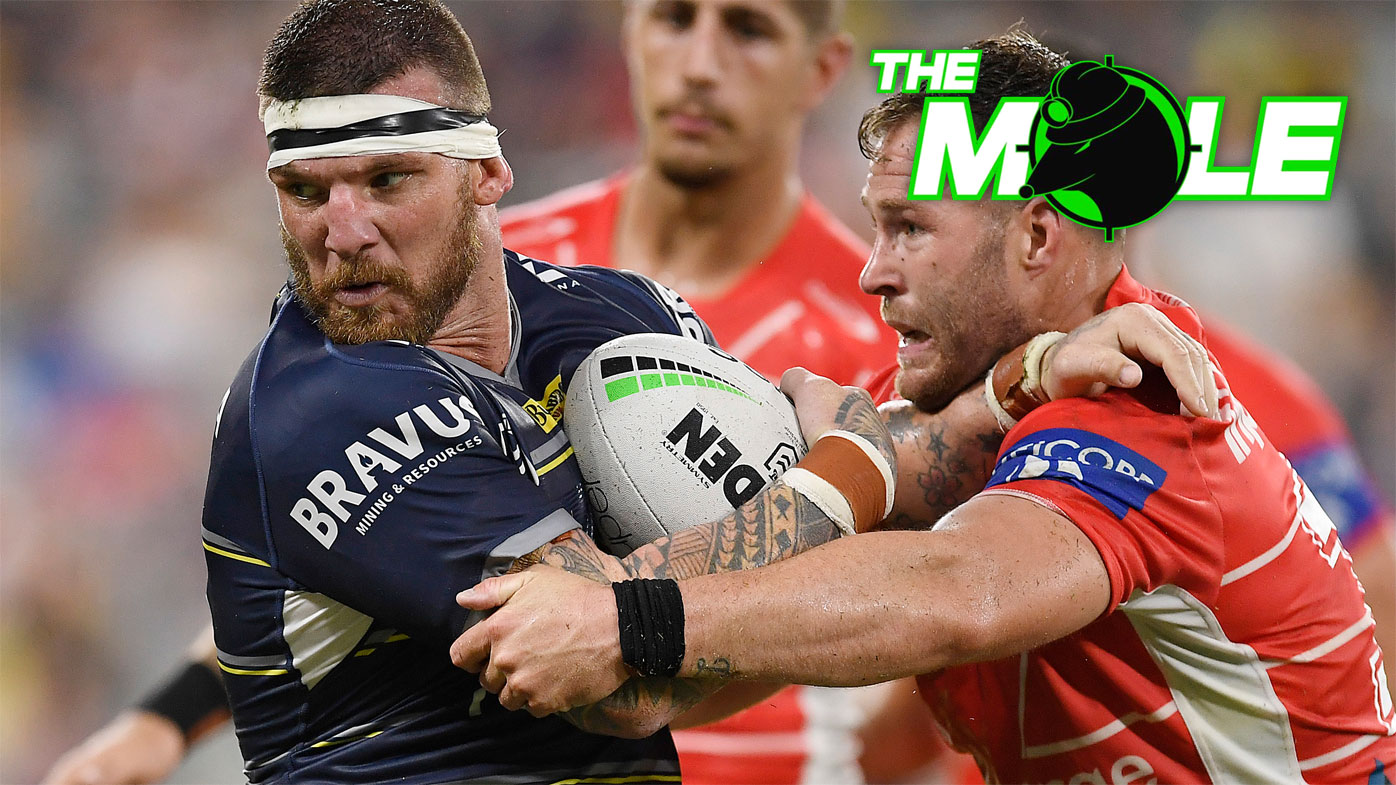 Cowboys star Josh McGuire is tackled by Dragons forward Trent Merrin.